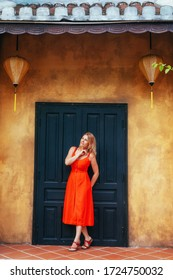 A beautiful girl in a red dress stands against the dark door of an old yellow house with Chinese lanterns.architecture of the ancient city of Hoi an .Vietnam.