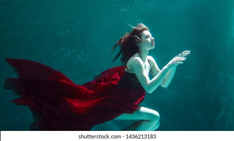 beautiful girl in a red dress swims under water. Underwater beauty shooting.