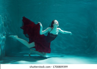 beautiful girl in a red dress swims under water. amazing Underwater beauty photo.