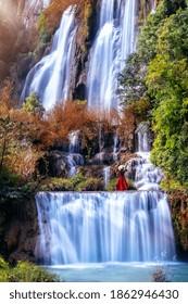 Beautiful girl in red dress at Thi Lo Su waterfall(Tee Lor Su) in Tak province. Thi Lo Su waterfall the largest waterfall in Thailand.
