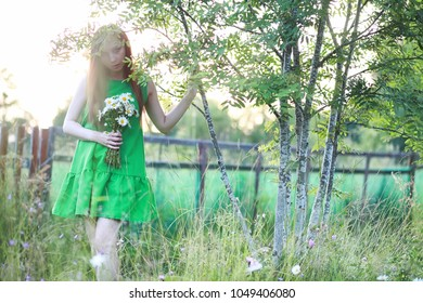 beautiful girl with red hair with a bouquet of daisies on the nature at home