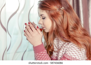 Beautiful girl with red hair drinking hot tea. In warm sweater, cozy scene
