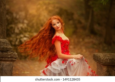 Beautiful girl with red hair in an elegant dress in the autumn park