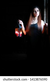 beautiful girl with red hair with a lantern in a dark room