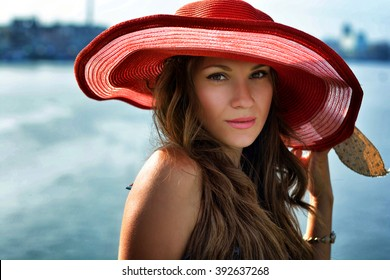 Beautiful girl in a red hat smiling at the summer waterfront
