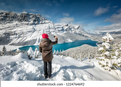 Beautiful girl with red hat taking picture with smartphone near Peyto Lake, Banff, Canada.