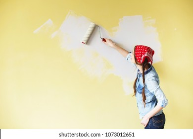 Beautiful girl in red Headband painting the wall with paint roller. Portrait of a young beautiful woman painting wall in her new apartment