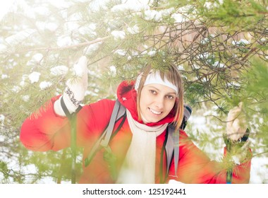 Beautiful girl in red jacket standing with backpack and ski poles. Happy smiling woman enjoys bright winter day. Winter snowy forest in background. Active sport and outdoor activity.