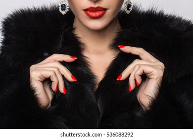 Beautiful girl with red lips in black fur coat.  Winter Girl in Luxury. Fashion Fur. Beautiful Woman in Luxury Fur Coat. Fashion model posing in a chinchilla fur coat