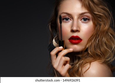 Beautiful girl with red lips and classic makeup and curls with mascara in hand. Beauty face. Photo taken in the studio.