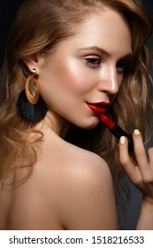 Beautiful girl with red lips and classic makeup and curls with lipstick in hand. Beauty face. Photo taken in the studio.