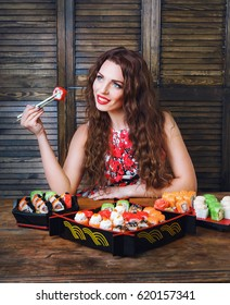 Beautiful girl with red lips eating sushi close-up. Woman with perfect make up holding sushi roll with chopsticks.