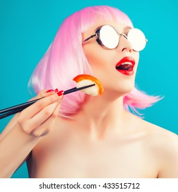Beautiful girl with red lips and pink hair eating sushi close-up