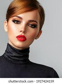 Schönes Mädchen mit roten Lippen und kurzen Haaren. Das Gesicht einer jungen sinnlichen Frau. Nahaufnahme eines Porträts eines Models mit heller Make-up auf einem Gesicht. Attraktive weibliche Haltung im Studio in schwarz zu schließen.