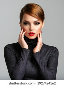 Beautiful girl with red lips and short hair. Pretty face of an young sensual woman. Closeup portrait of a model with bright makeup on a face. Attractive female posing at studio  in black closes.
