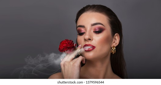 beautiful girl with red lips and smoky eyes makeup holds a rose in her hands and smoke