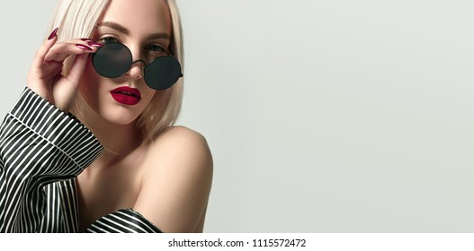Beautiful girl with red lipstick and blond hair in silk pajamas in black and white stripes and in round sunglasses.