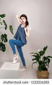 Beautiful girl with red lipstick and dark hair in a cotton top in polka dots and jeans on a beige background.