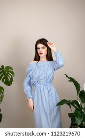 Beautiful girl with red lipstick and dark hair in a cotton dress striped on a beige background. Against the background of the leaves of monsters and spathiphyllum.