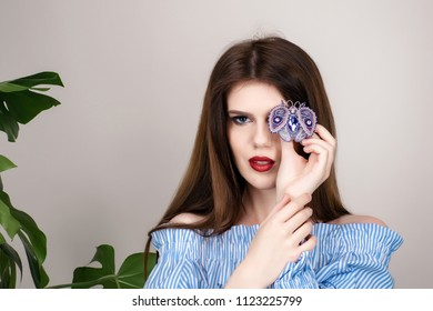 Beautiful girl with red lipstick and dark hair in a cotton dress striped on a beige background. Against the background of the leaves of monsters and spathiphyllum. Girl holds jewelry from beads.