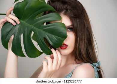 Beautiful girl with red lipstick and dark hair in a green cotton dress on a beige background. Against the background of the leaves of monsters and spathiphyllum.