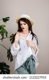 Beautiful girl with red lipstick and dark hair in a straw hat, shorts and a white cotton shirt on a beige background. Against the background of the leaves of monsters and spathiphyllum.