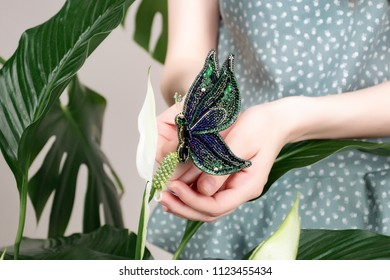 Beautiful girl with red lipstick and dark hair in light clothes on a beige background with leaves of a monster and spathiphyllum.