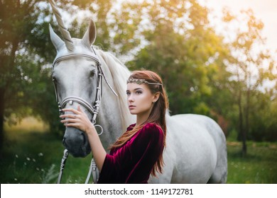Beautiful girl in red medieval dress with unicorn. Fantasy. Woman Elf