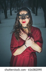 Beautiful girl in a red winter dress in a mask