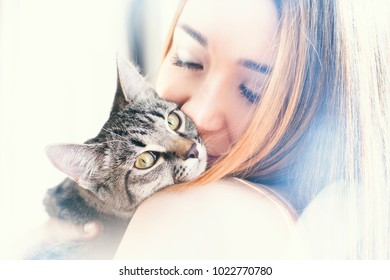 Beautiful girl with redheads hair playing with a gray cat