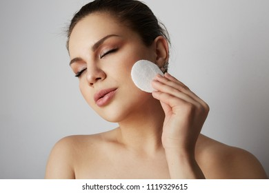 Beautiful girl refreshing skin face with white cotton pads over gray studio background.Model with light nude make-up.Healthcare skin makeup concept