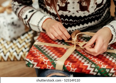 Beautiful girl in reindeer winter sweater unwrapping christmas present with golden ribbon, hands close-up, greeting card concept. christmas shopping.