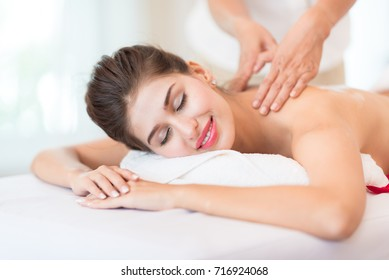 Beautiful Girl Relaxes in the Spa Salon.Woman Lying with closed eyes and having a wellness back massage and feeling visibly good.Healthy Lifestyle and Relaxation Concept.