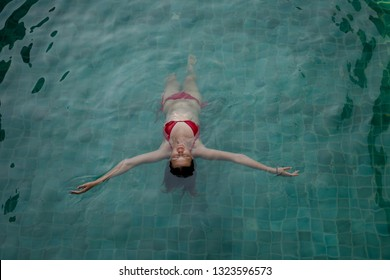 beautiful girl relaxes in the swimming pool in sunny day. enjoying relax in hotel pool during her summer weekend.