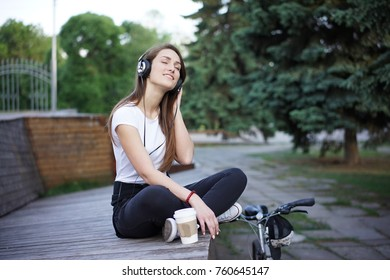 Beautiful girl relaxing and listen music in the headphones in the city park on blurred background. Young woman listening music outdoor.