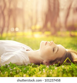 beautiful girl relaxing lying on the grass in the garden