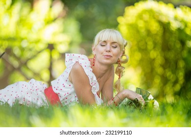 Beautiful girl is relaxing lying on the grass in the garden