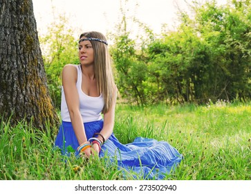 Beautiful girl is relaxing lying on grass in the garden