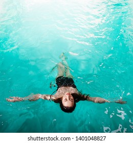 beautiful girl is relaxing in the Spa pool,swim and relax. young woman floating in water on the back, copy space