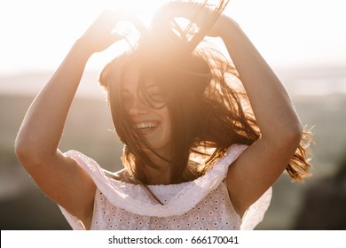 Beautiful girl remains on top of a mountain and looks at the horizon with a beautiful background. A colorful photo of a natural sunset, a miracle, incredible, a dance, hair in the wind.