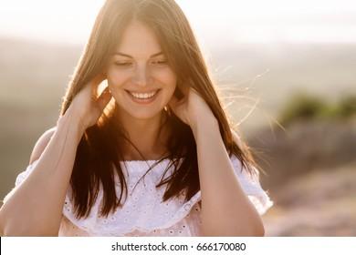Menina bonita permanece no topo de uma montanha e olha para o horizonte com um fundo bonito. Uma foto colorida de um pôr do sol natural, um milagre, incrível, uma dança, cabelo ao vento.
