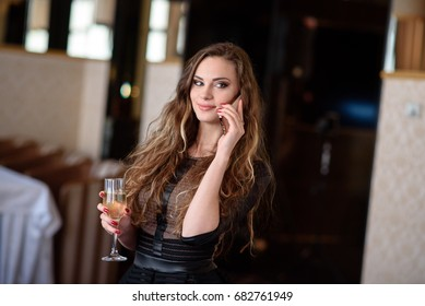 A beautiful girl in a restaurant communicates by phone.