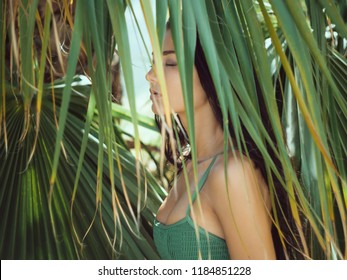 Beautiful girl resting and enjoying vacation in tropical forest. Close-up of sensual young brunette mixed race Asian Caucasian woman wearing swimsuite with perfect tan wet hair with closed eyes under