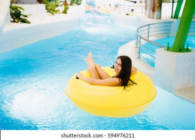 Beautiful girl is resting on an inflatable ring in the water park. Smiling and laughing. The sun. aquapark