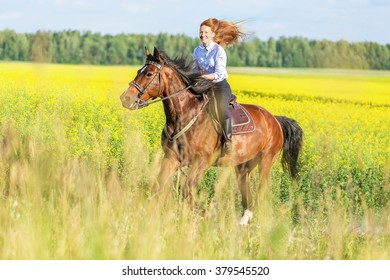 Beautiful girl riding gallop in blooming meadow.