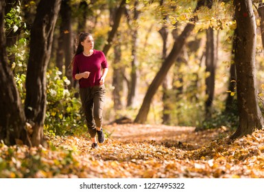 Beautiful girl running trough forest in autumn