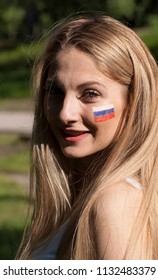 A beautiful girl with a Russian flag drawn on her cheek. Football cheerleader. Portrait close-up.