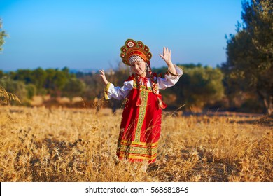 Beautiful girl in Russian folk costume dancing at field
