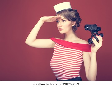 beautiful girl sailor with a vintage binoculars and looks into the distance