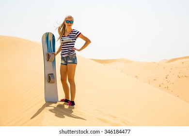Beautiful girl sand boarding down the dunes in a desert near Arab Emirates
